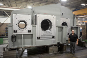 Man standing next to large machined part